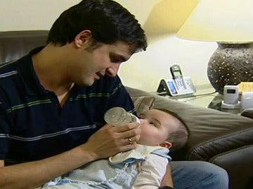 Un padre da el biberón a su bebé