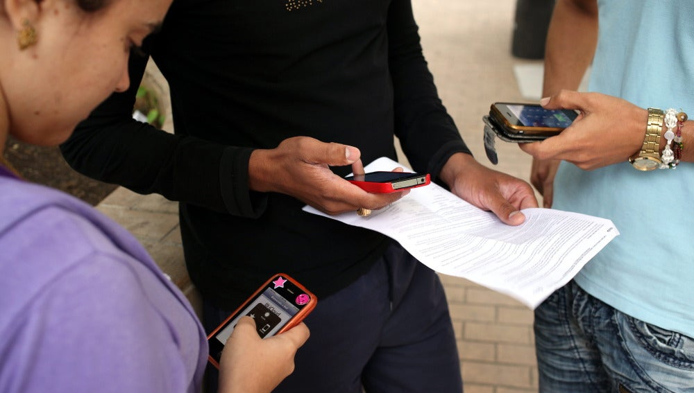 Varias personas con sus teléfonos móviles