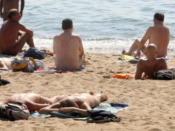 Varias personas practican nudismo en una playa