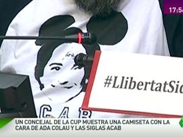 Un concejal de la CUP muestra una camiseta con la cara de Ada Colau y las siglas ACAB