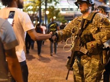 Un manifestante saluda a un efectivo de la Guardia Nacional