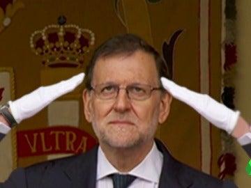 A falta de paraguas que le resguarde de la lluvia, a Mariano Rajoy le tapan de otra forma que no parece convencerle...
