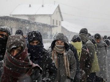 Migrantes esperan en fila para recibir comida fuera de un almacén abandonado en Belgrado