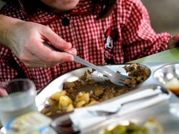 Una niña almorzando en un comedor escolar.