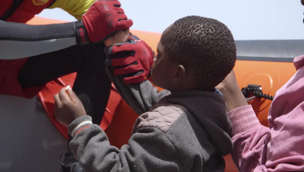 Un niño refugiado comparte un chicle con un voluntario