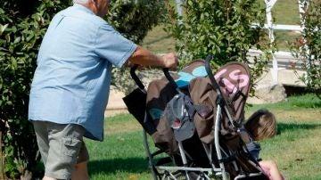 Un abuelo paseando a sus nietos