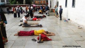 Budistas tibetanos postrados ante el templo de Jokhang, en Lhasa. Foto: Marino Holgado