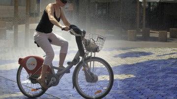 Una joven se refresca en una fuente subida en una bicicleta