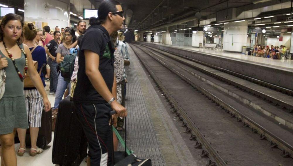 Los viajeros esperan la llegada de un tren