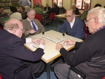 Varios jubilados juegan al dominó