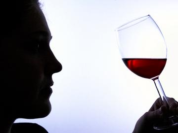 Un hombre bebe vino tinto