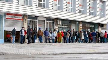 Varias personas forman cola ante una oficina del INEM.