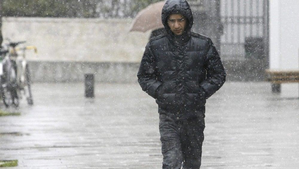 Un hombre camina por una calle de Vitoria mientras nieva