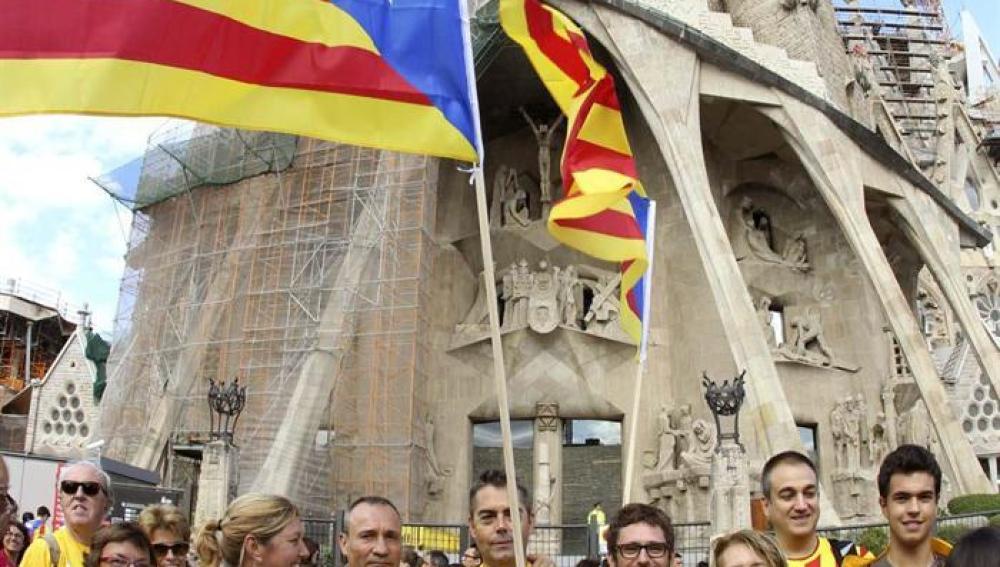 Varias personas congregadas frente a la Sagrada Familia participan en la cadena humana