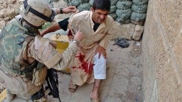 Un soldado atiende a un herido civil tras un ataque suicida que mató a 33 en Tall Afar (2005).