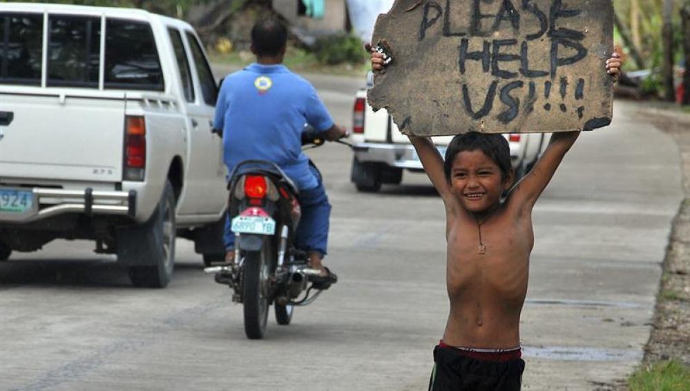 Un niño pide ayuda a los automovilistas en una zona devastada por el paso tifón Haiyan
