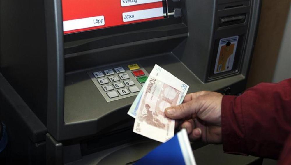 Un hombre retira euros de un cajero automático