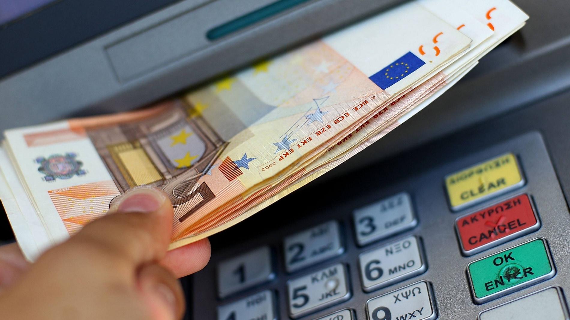 Un usuario recoge efectivo de un cajero automático