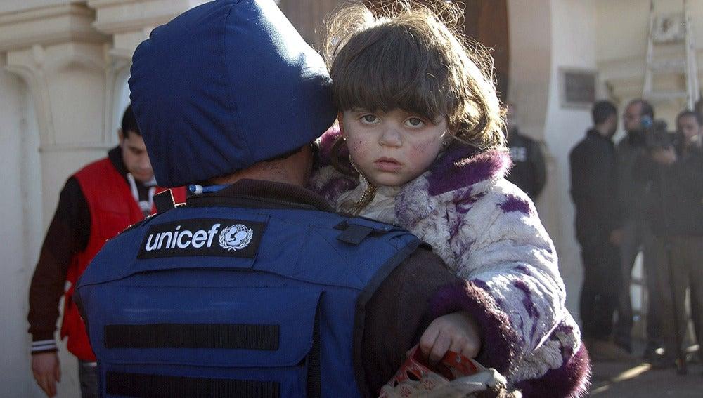 Un miembro de UNICEF lleva en brazos a una niña siria en un refugio situado en la ciudad de Homs