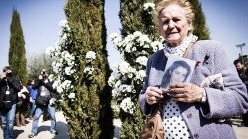 Una mujer sostiene una foto de una de las víctimas