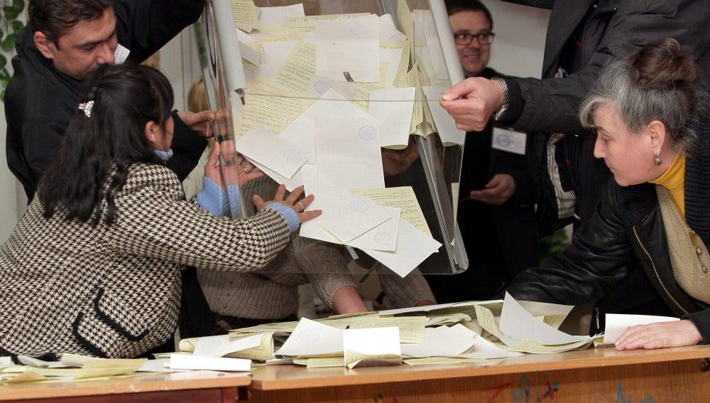 Los miembros de una comisión electoral local vacian una urna para contar los votos en un colegio electoral en Simferopol, Crimea