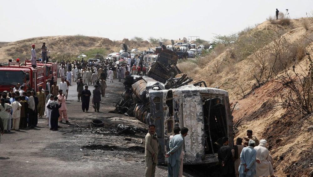 Varias personas inspeccionan los restos de los autobuses accidentados cerca de la ciudad de Hub