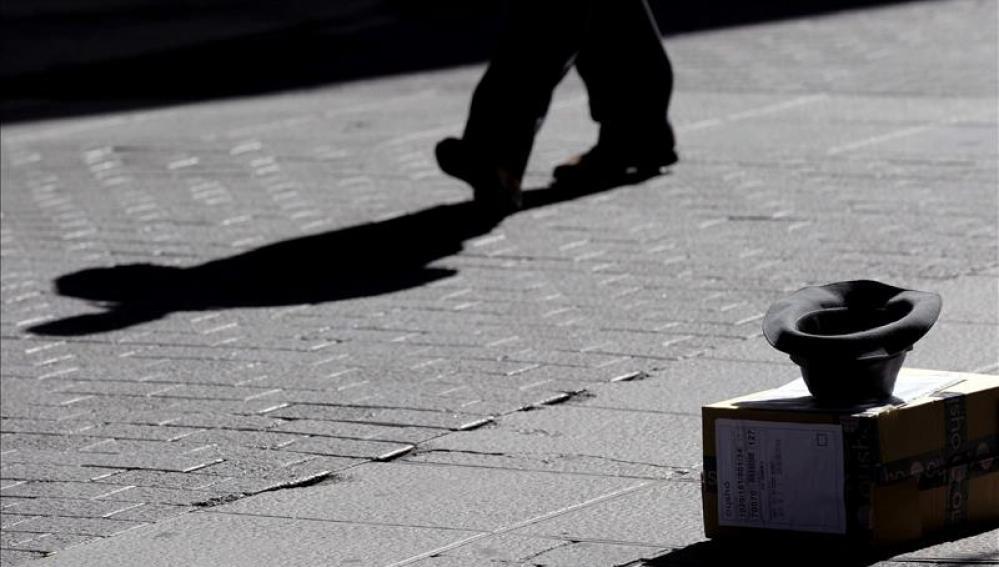 Una persona pidiendo dinero en la calle