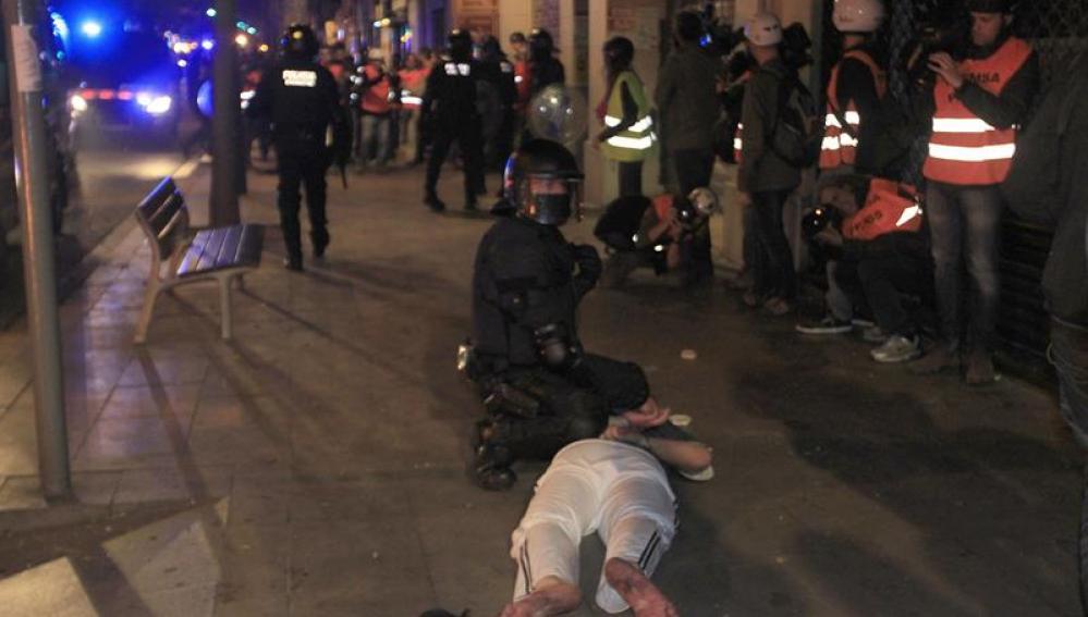 Un Mosso deteniendo a un manifestante