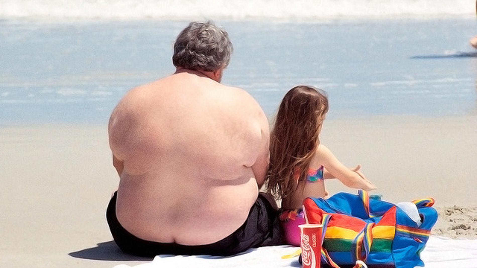 Un hombre obeso descansa en una playa co