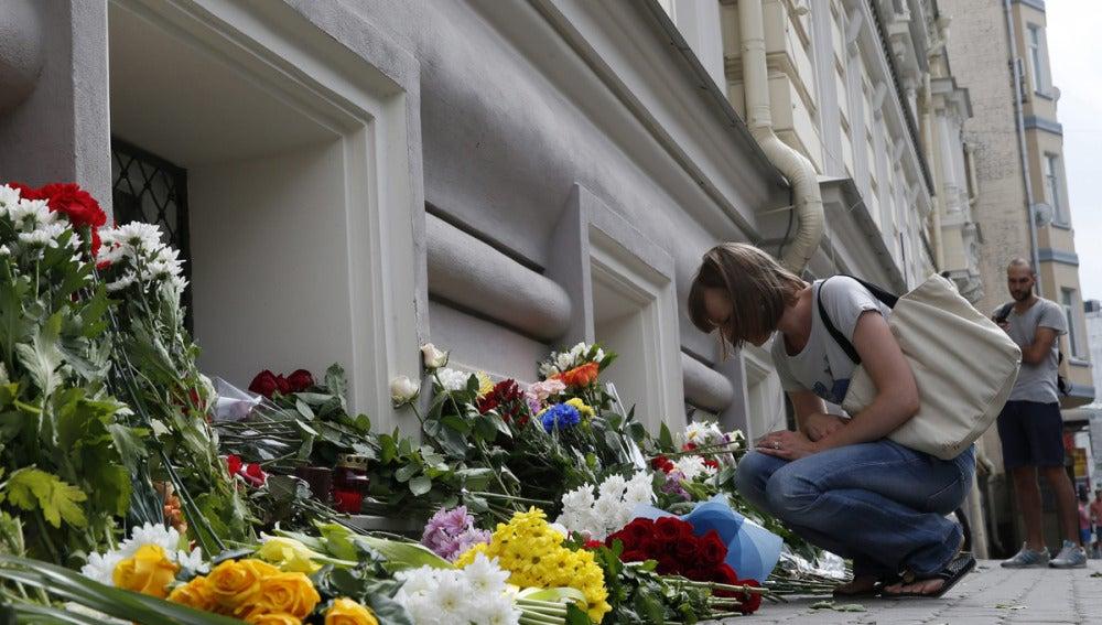 Una mujer deposita flores colocadas a las puertas de la Embajada de Holanda en Moscú