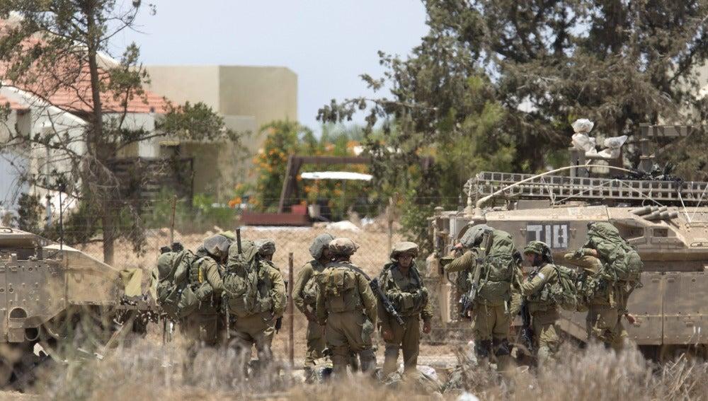 Miembros de la infantería del Ejército israelí permanecen cerca de un tanque de combate