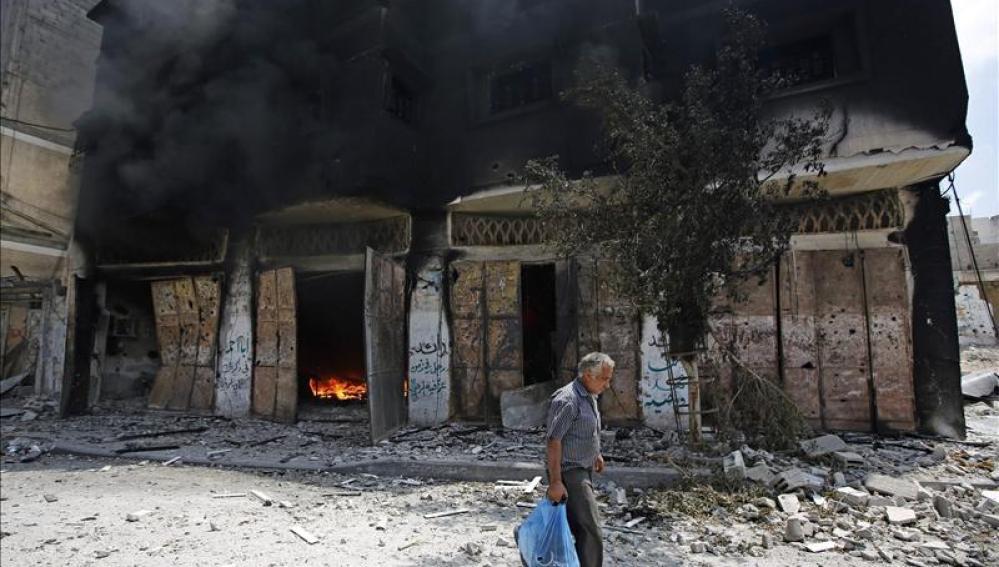 Un palestino huye de su casa en el barrio de Al Shejaeiya