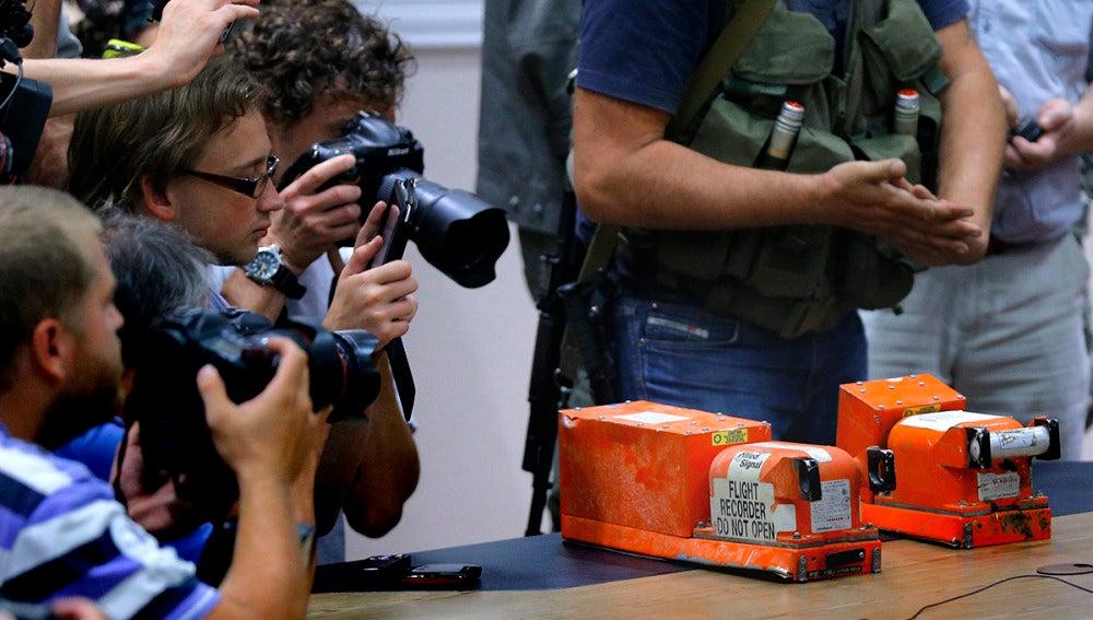 Periodistas toman imágenes de las dos cajas negras del vuelo MH17