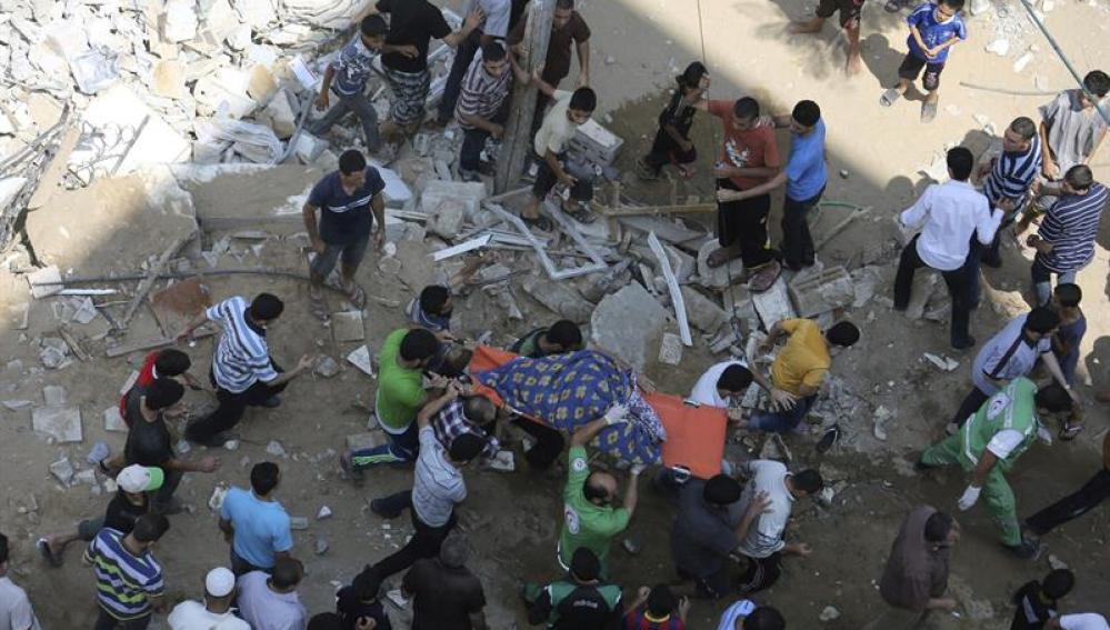 Palestinos con el cuerpo de una mujer encontrada entre escombros
