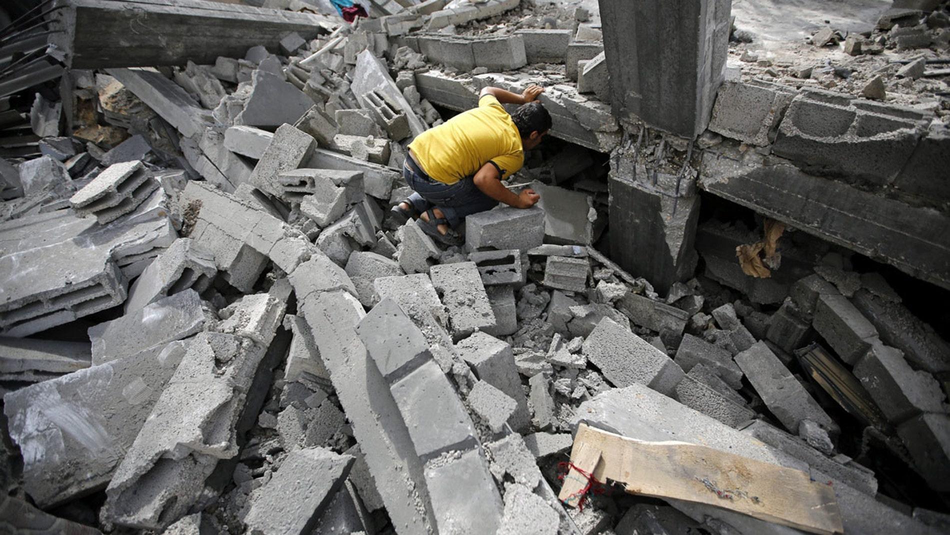 Un palestino busca entre los escombros tras un bombardeo israelí