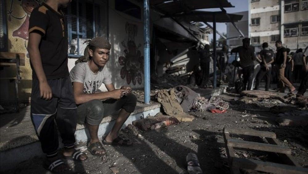 Jóvenes palestinos sentados junto a un aula destruida
