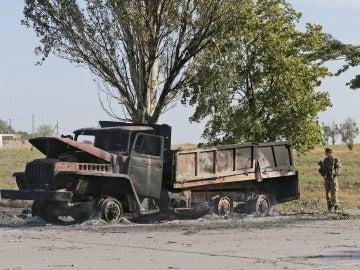 Un soldado ucraniano hace guardia junto a un camión militar calcinado en Mariupol