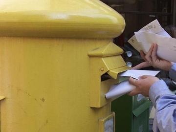 Un ciudadano deposita cartas en un buzón de Correos