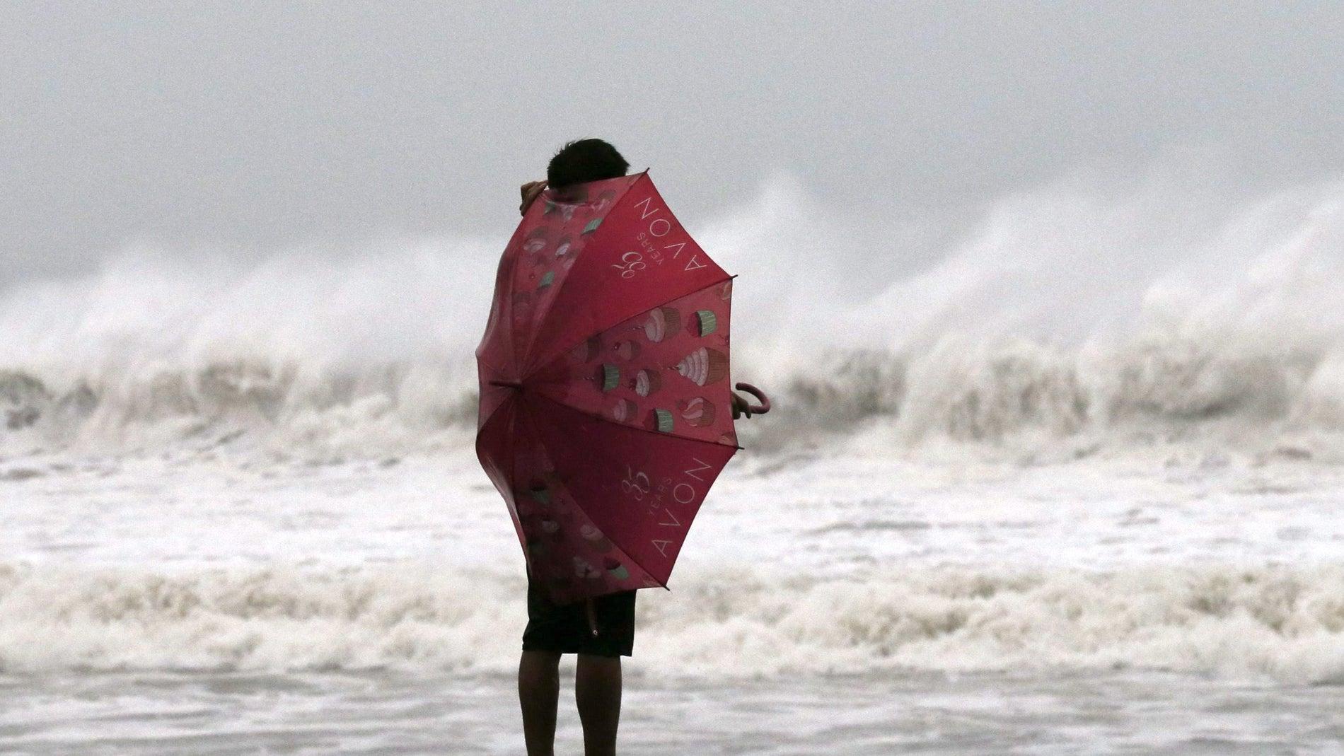 Una mujer se protege del viento del tifó