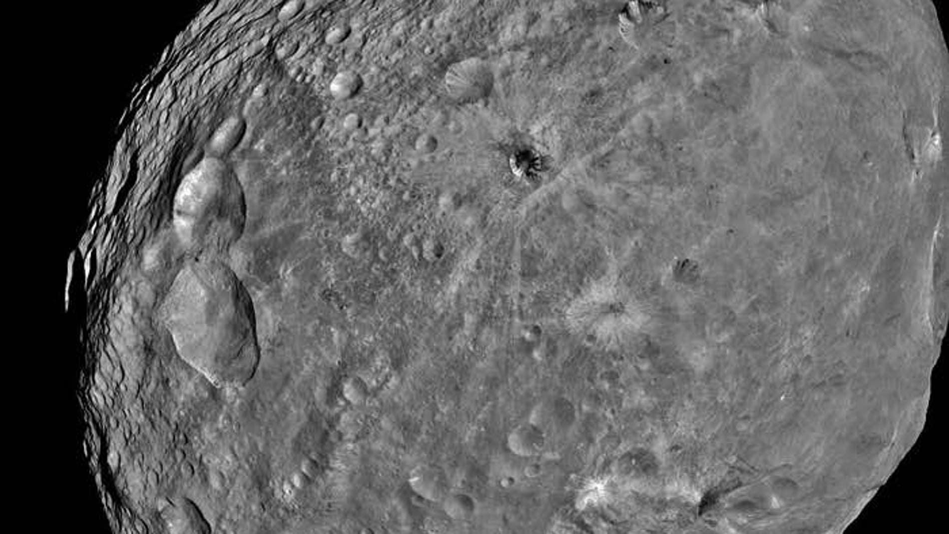 Cráter Cornelia en Vesta. A la derecha se ven los barrancos con los bordes curvados y el depósito con forma de abanico
