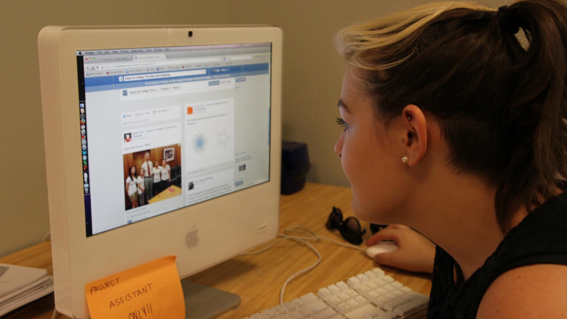 Una estudiante delante de una pantalla con Facebook