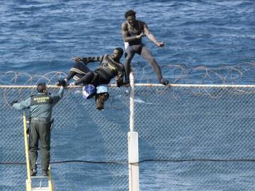 Imagen de archivo en la que dos inmigrantes intentan saltar la valla en Ceuta