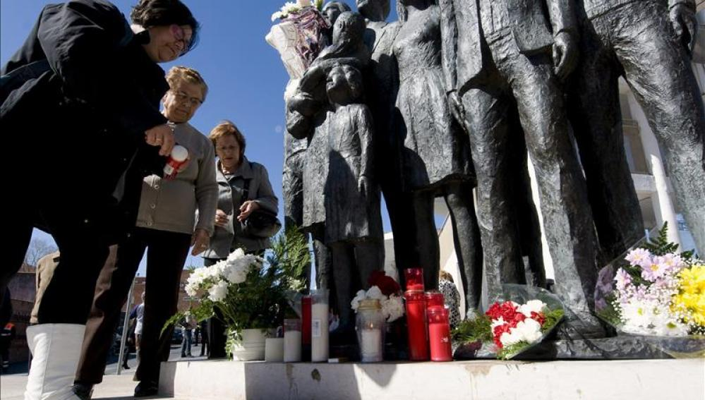 Varias personas depositan flores y velas junto al monumento en memoria de los fallecidos del 11M