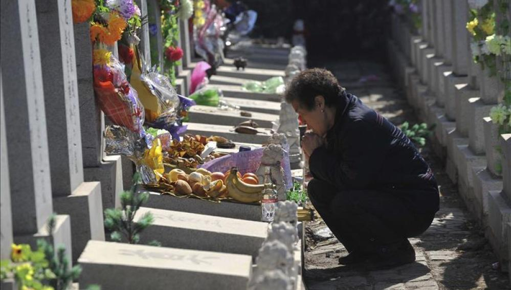 Una mujer reza junto a la tumba de un familiar en un cementerio.