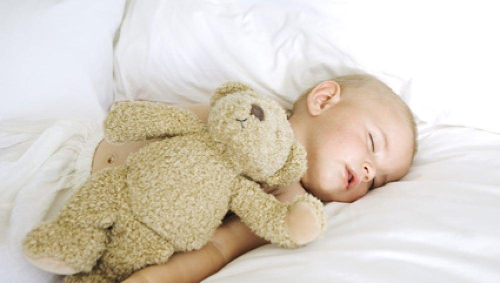 Un bebé dormido junto a un osito de peluche.
