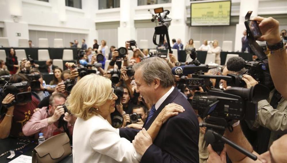 Manuela Carmena, alcaldesa de Madrid, saluda al candidato socialista, Antonio Miguel Carmona, a su llegada al Palacio de Cibeles para el acto de constitución del Ayuntamiento.