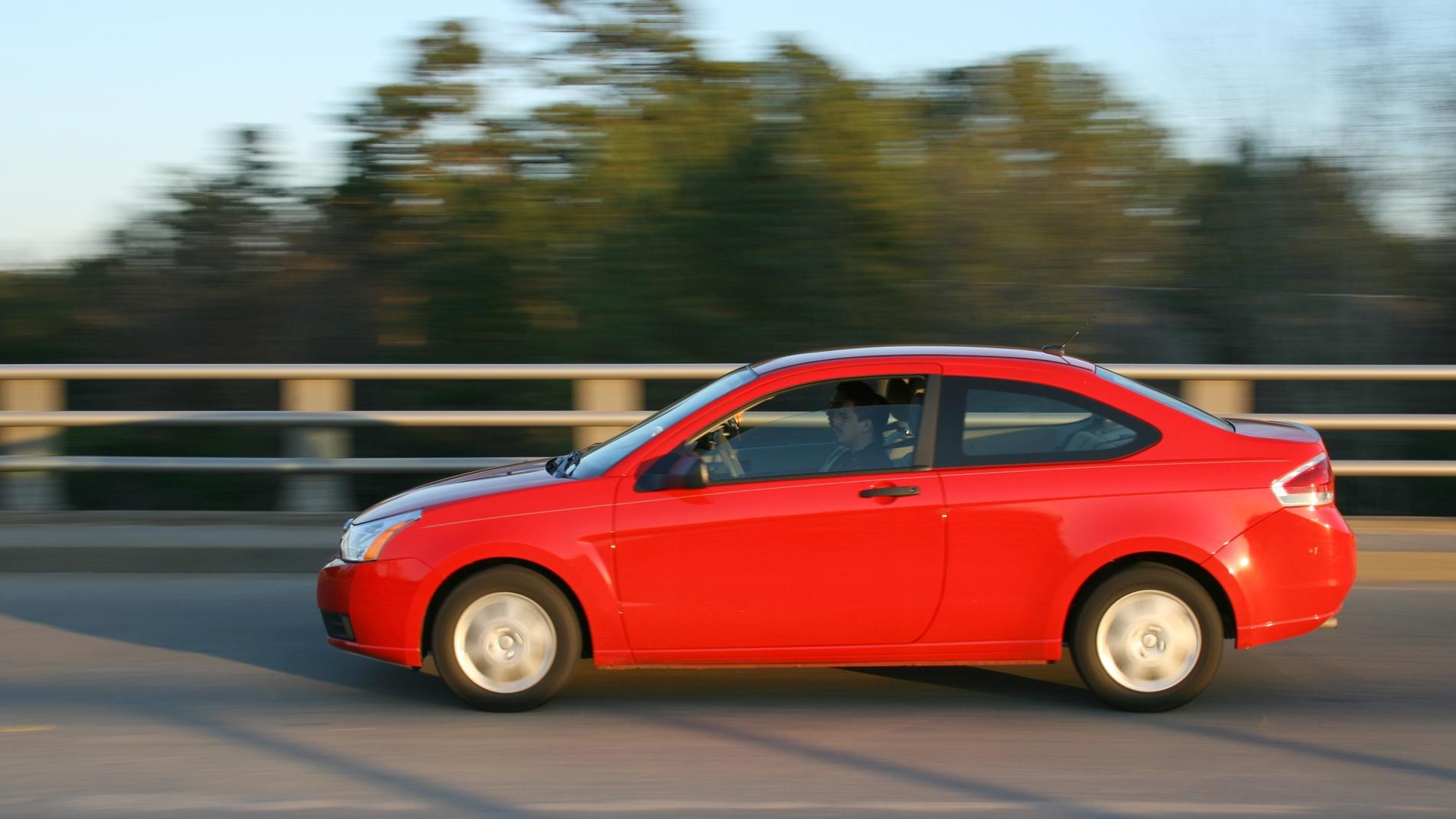 Un coche rojo circula por la carretera (