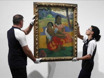 """Dos operarios cuelgan el cuadro de Paul Gauguin """"Nafea faa ipoipo"""""""
