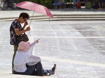 Dos turistas se protegen del calor.