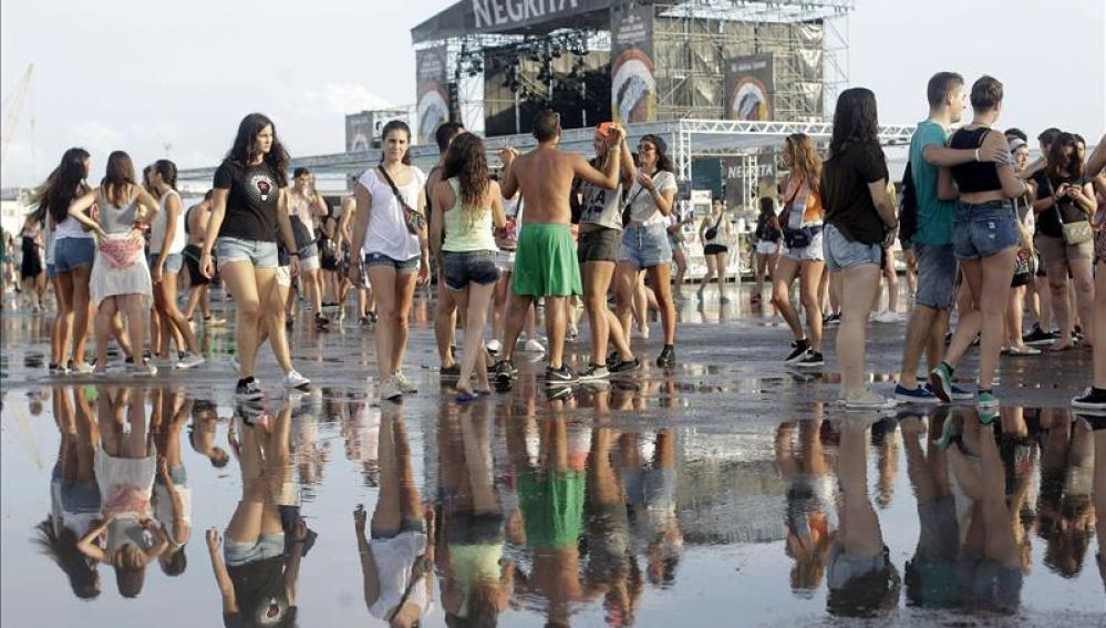 Varias jóvenes tras la tormenta registrada en la primera jornada grande del festival Arenal Sound